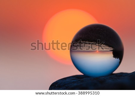 Coast reflected inside the crystal ball at sunset - stock photo