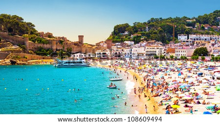 Coast with tanning and bathing people (Panorama of Costa Brava, Tossa de Mar city, Spain) - stock photo