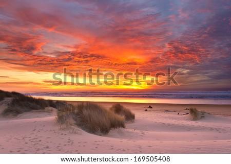 Coastal Beach Sunset Sky and Sand Dunes - stock photo