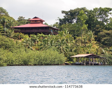Coastal home with tropical garden and a boathouse over water, Panama, Caribbean sea - stock photo