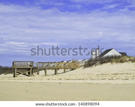 Coastal landscape: Beach view of boardwalk and deck by dune near peaked roofs of houses in Cape Cod, Massachusetts - stock photo