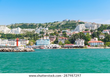Coastal landscape of Balchik resort town. Entrance to port, red lighthouse on the pier. Coast of the Black Sea, Varna region, Bulgaria