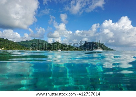 Coastal landscape of Huahine island near the village of Fare, seen from calm water surface of the lagoon, Pacific ocean, French Polynesia - stock photo