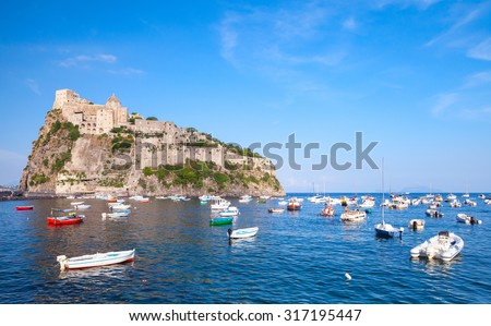 Coastal landscape of Ischia port with Aragonese Castle and small wooden boats