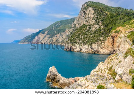 coastal landscape with blue sea and beautiful cliffs an mountains - stock photo