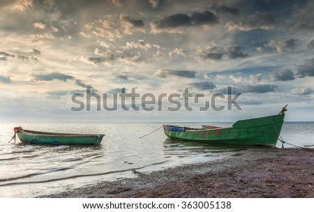 Coastal landscape with boats anchored at a beach of the Baltic Sea, Latvia - stock photo