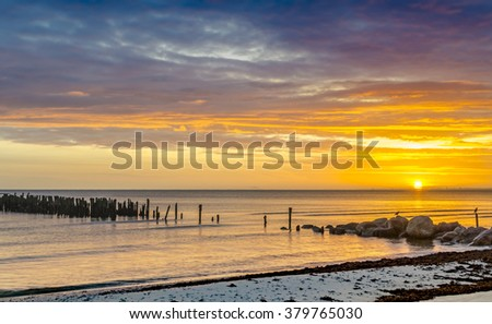 Coastal landscape with old broken pier and colorful sunrise, Baltic Sea - stock photo