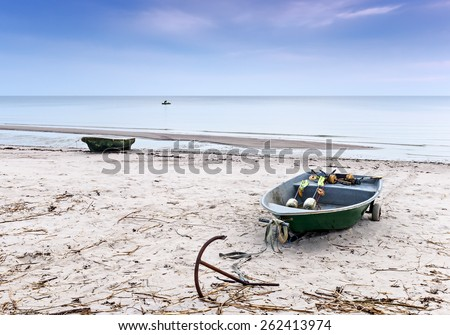 Coastal landscape with small fishing boats on sandy beach and lonely fisherman at horizon, Baltic Sea, Latvia, Europe - stock photo