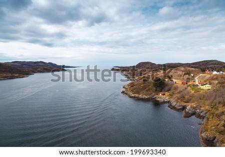 Coastal Norwegian village landscape. Colorful wooden houses on rocks - stock photo
