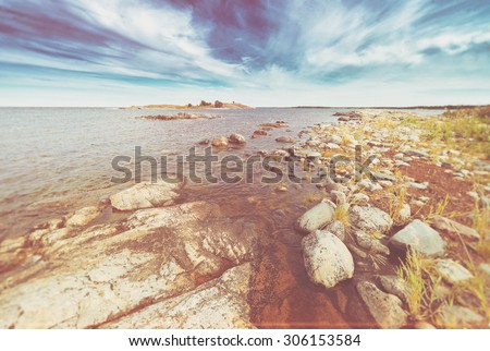 Coastal scene with vegetation on the round rocks at seafront during summer. Filters applied - stock photo