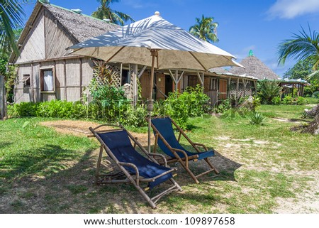Coastal straw house with deck chairs and parasol in Sainte-Marie island - stock photo