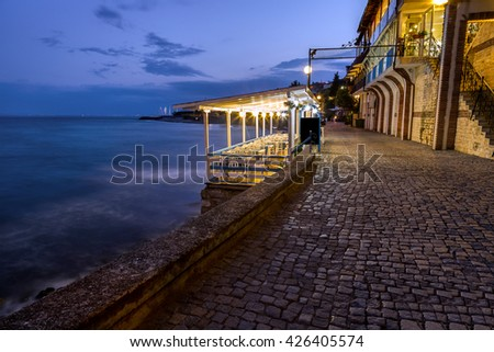 Coastal street with restaurants at night - stock photo