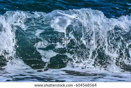 Coastal transparent sea/ocean crashing wave with foam on its top