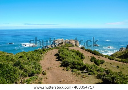 Coastal view onto the Muelle de las Almas with a clear blue sky and green hills