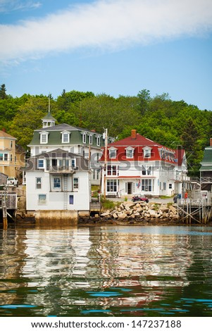 Coastal village in Maine, viewed from the water with reflections - stock photo