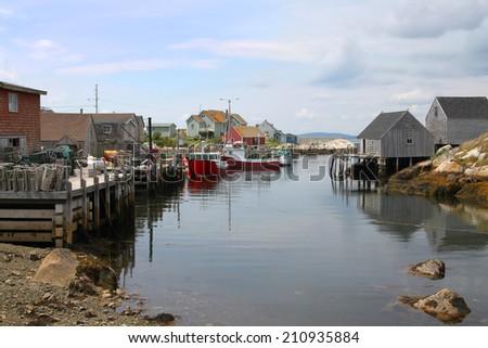 Coastal village of Peggys Cove, Nova Scotia, Canada, showing seaside shacks, fishing boats, and houses along the coast - stock photo