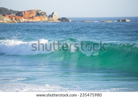 Coastline along the Bay of Fires, Tasmania, with orange colored rocks in the blurred background, turquoise shimmering ocean with big waves and copy space. - stock photo