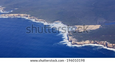 coastline and green forest covered land terrain meets blue sea waters with white surfing waves aerial view from the mid-air  - stock photo