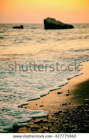 Coastline before sunset near Petra Tou Romiou, vintage look. Paphos District, Cyprus. Shallow depth of field. - stock photo