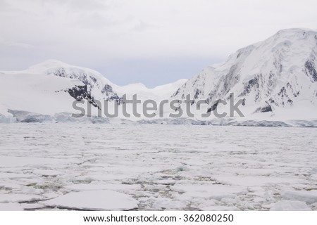 Coastline of Antarctic Peninsula with glacier packed with field of floating ice.