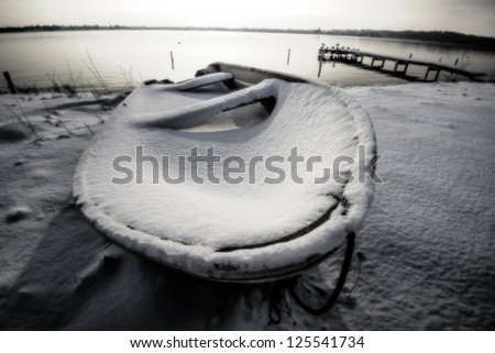 Coastline smal boat and snow all over. - stock photo