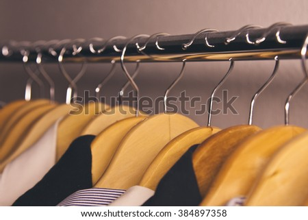 coat rack with clothes on hangers hanging - stock photo