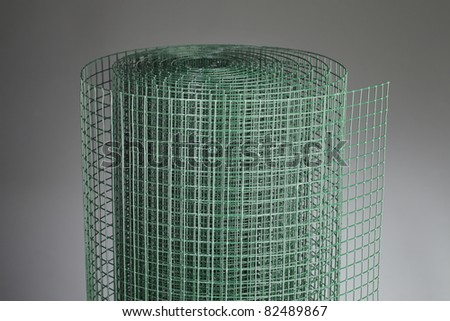 Coated green metallic wire mesh used in gardening by protecting plants from animals. - stock photo