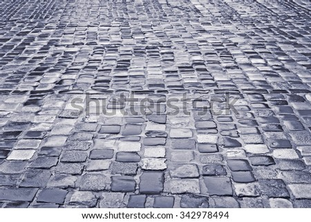 Cobbled road with wet cobblestones in rainy weather in downtown of Lviv, Ukraine, photo edited to black and gray - stock photo