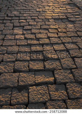 Cobblestone pavement at evening sunlight background texture - stock photo