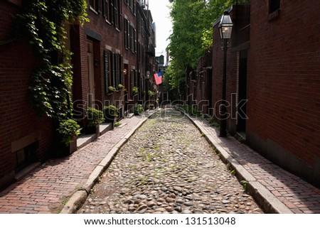Cobblestone road leads to American Flag on historic Beacon Hill, Boston, MA - stock photo