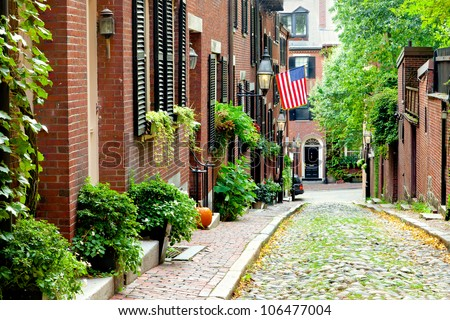 Cobblestone street in Boston.  Historic Acorn Street in Beacon Hill, called the most picturesque street in America, with a row of vintage red brick buildings. - stock photo