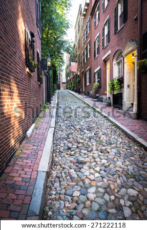 Cobblestones and traditional red brick houses on Acorn street. Old Glory is placed on one of homes in famous landmark and sightseeing place, oldest street in Boston. - stock photo