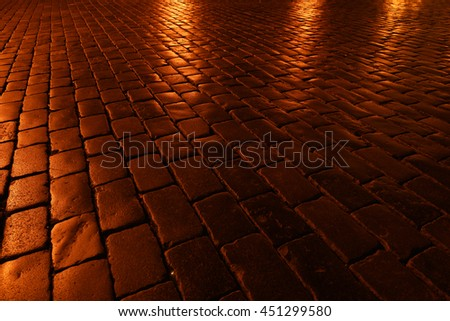Cobblestones with night lights. Stone texture.