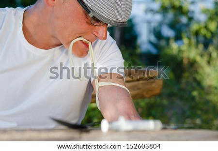 Cocaine addict tying off his arm to raise the veins so that he can inject the liquid drug using a syringe - stock photo