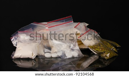 Cocaine and marihuana in packages on black background - stock photo