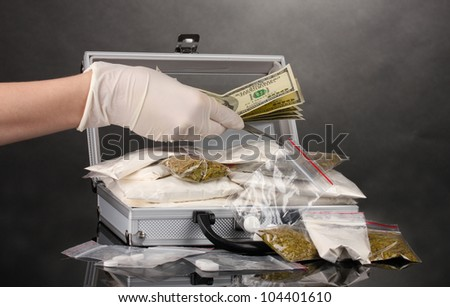 Cocaine and marijuana in a suitcase wiht hand isolated on white - stock photo