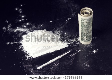 cocaine dose and rolled dollar on table