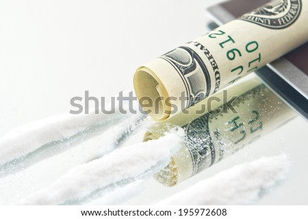 Cocaine drug powder lines and rolled up USA hundred dollar bill for sniffing. Drug addiction concept.