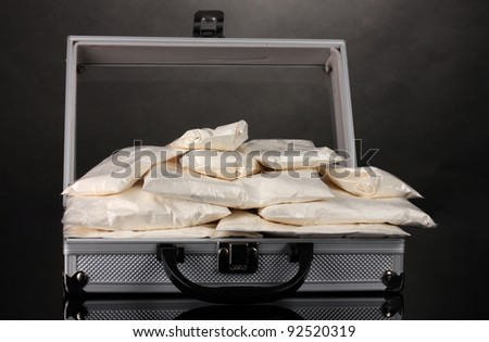 Cocaine in a suitcase on grey background - stock photo