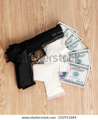 Cocaine in packages, dollars and handgun on wooden background