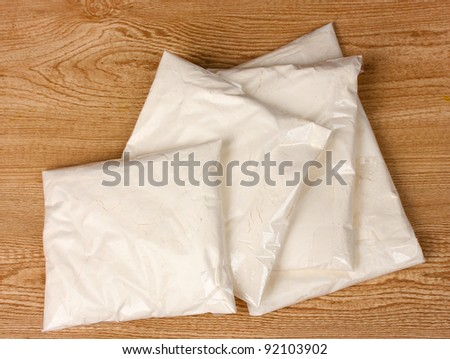 Cocaine in packages on wooden background - stock photo