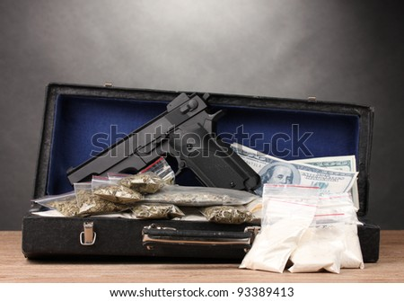Cocaine, marijuana dollars and handgun in case on wooden table on grey background - stock photo