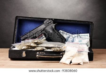 Cocaine, marijuana dollars and handgun in case on wooden table on grey background