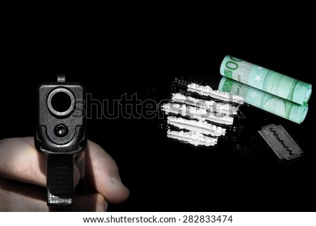Cocaine powder in lines, money and razor blade with gun in the hand ready to shoot on foreground. Image done on the black background  - stock photo