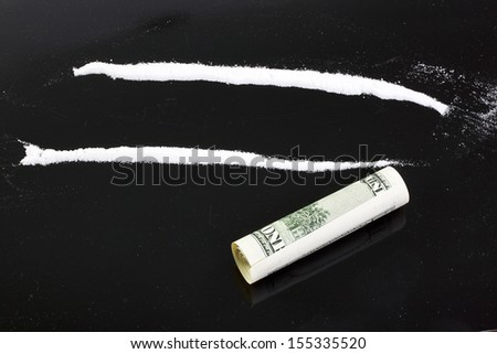 cocaine powder in lines on a black background - stock photo