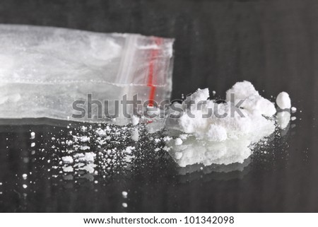 Cocaine powder pile  and packet on mirror - stock photo