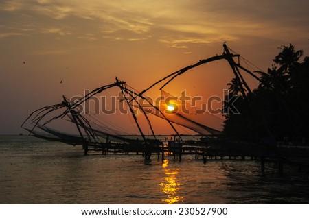 Cochin's famous Chinese Fishing nets seen at sunset - stock photo