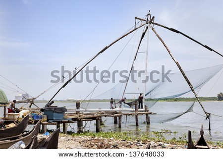 COCHIN-SEPTEMBER 05: Men work in the Chinese fishing net. Using ropes, they hold the counterweights that allows them to get on and off the fishing net on september 5, 2012 in Cochin, Inda