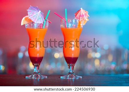 Cocktail. Alcohol drinks and cocktails on bar. colored light - stock photo