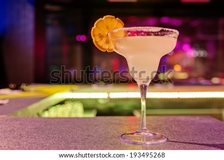 cocktail at bar in a night club with vivid colors - stock photo